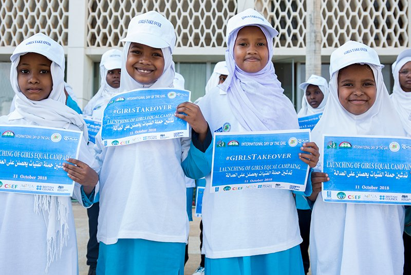 Sudanilaiset tytöt hymyilevät koulupuvuissaan ja pitävät käsissään papereita, joissa on tekstiä.