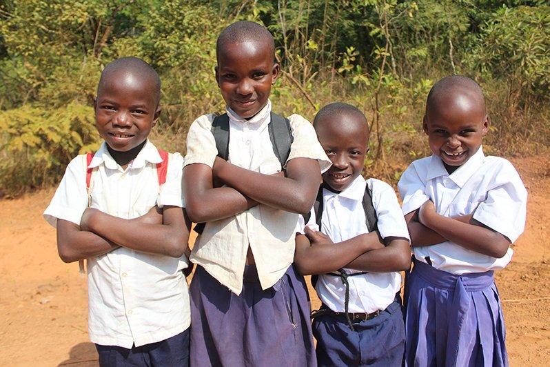 Tansanialaiset lapset seisovat ulkona koulupuvuissa kädet puuskassa ja katsovat kohti kameraa.