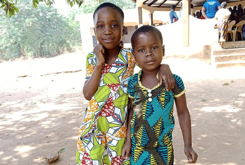 Kaksi togolaista lasta seisoo pihalla kädet toistensa ympärillä ja katsovat kameraan.
