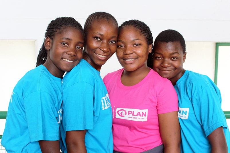 Ryhmä zimbabwelaisia nuoria hymyilee kameralle värikkäät paidat yllään.