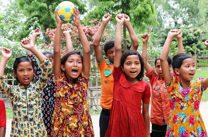 Bangladeshilaiset lapset ovat nostaneet kädet ylös ja poseeraavat kameralle.