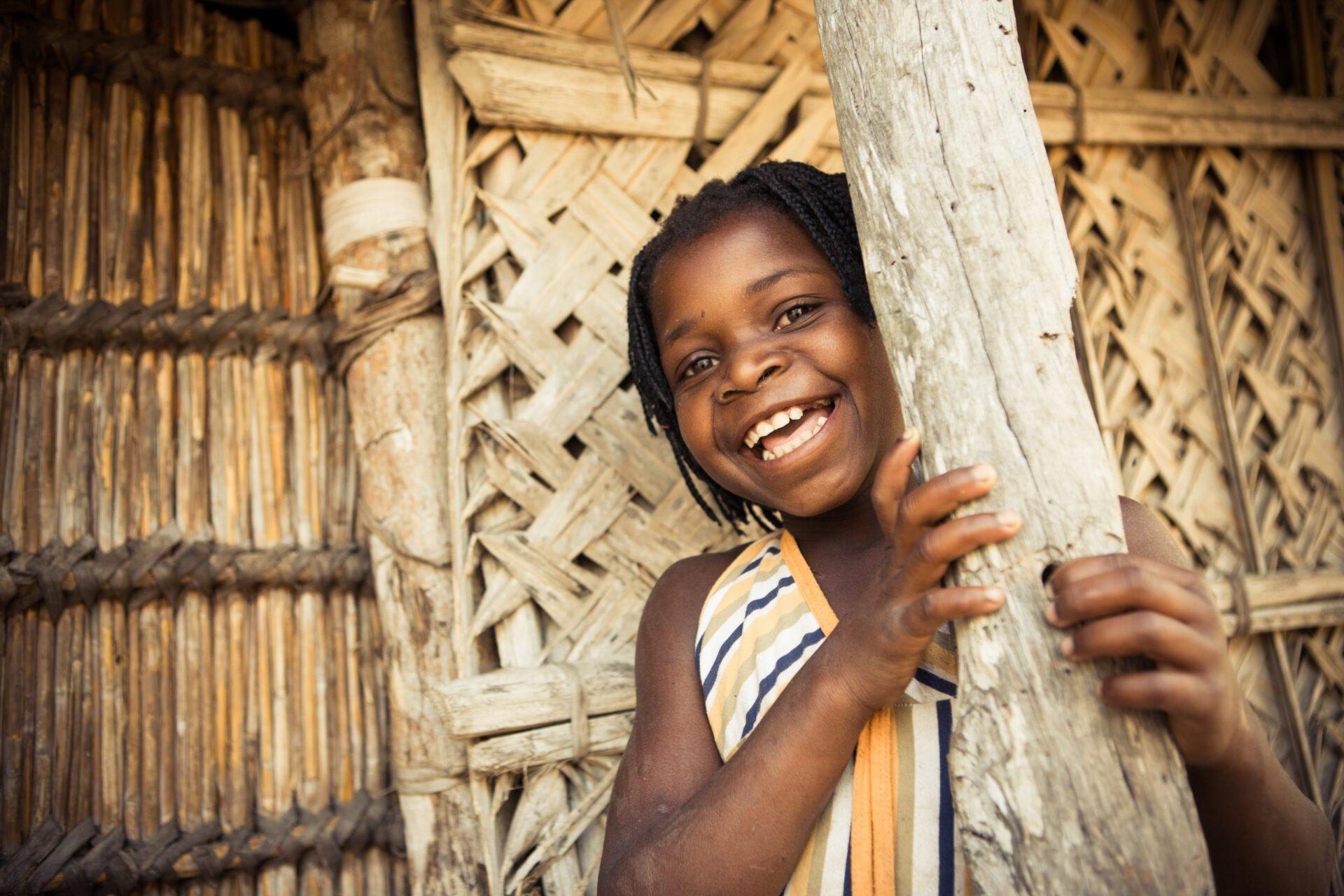 Mosambikilainen tyttö nojaa pylvääseen ja hymyilee.