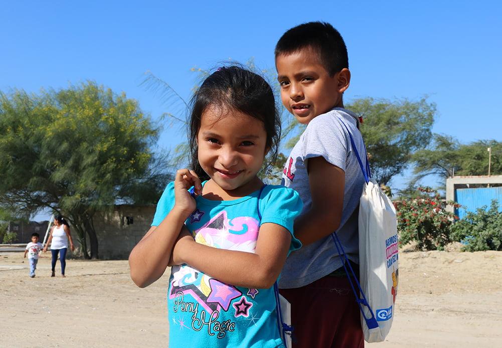 Aukiolla seisoo kaksi perulaista lasta, joista toisella on selässään Planin antama koulutarvikepakkaus.