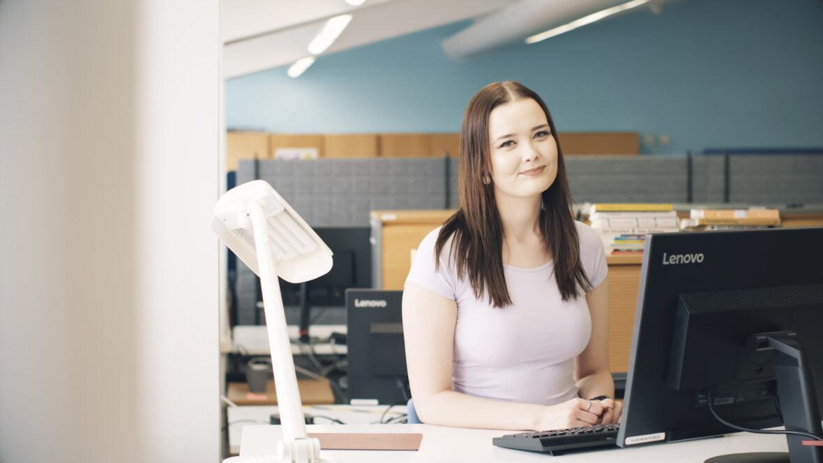 Planin työntekijä hymyilee ja tekee töitä tietokoneella