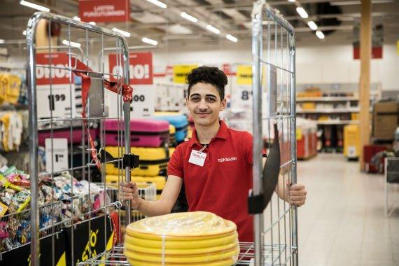 Nuori mies työntää rullakkoa myymälässä.