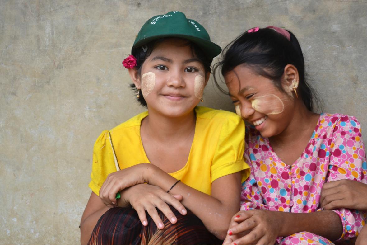 Kaksi tyttöä istuu vierekkäin ja nauraa.