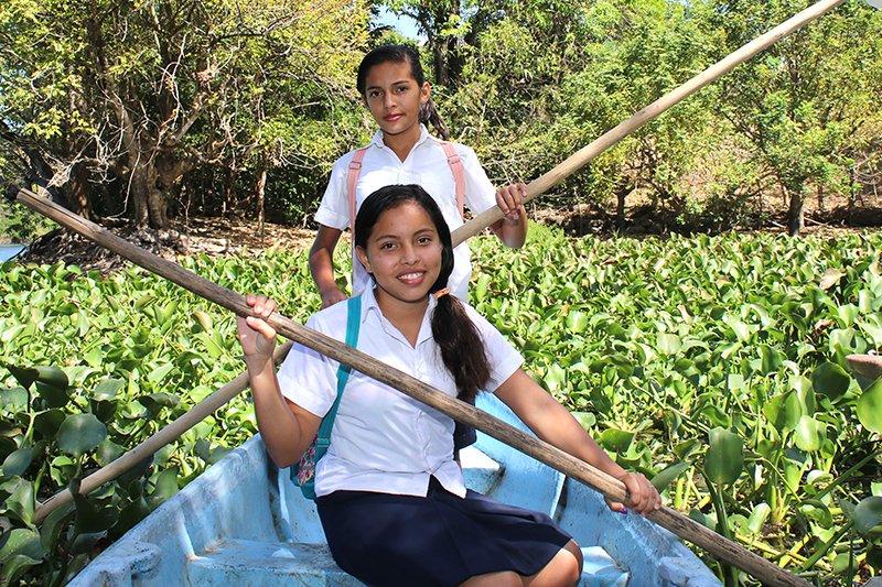 Kaksi tyttöä ohjaa venettä joessa kasvillisuuden keskellä.