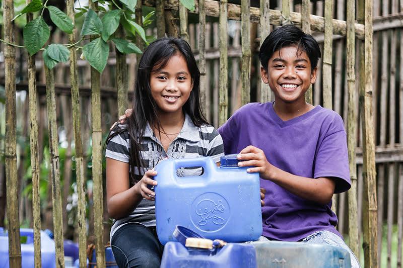 Filippiiniläiset sisarukset pitelevät vesikanisteria ja hymyilevät kameralle.