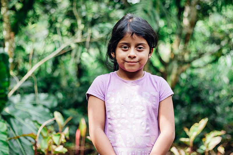 Guatemalalainen tyttö seisoo vehreässä maisemassa.