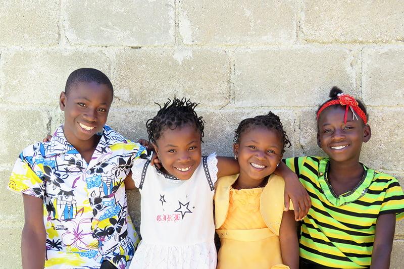 Haitilaiset lapset poseeraavat kameralle seinän edessä.