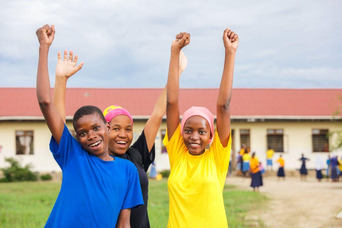 Kolme tansanialaistyttö iloisina kädet ylhäällä koulun pihalla.