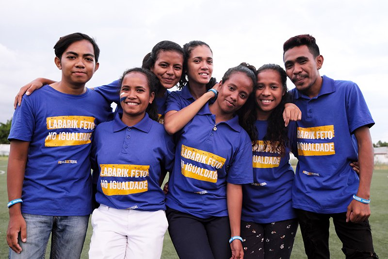 Ryhmä itätimorilaisia nuoria seisoo hymyillen samanlaiset siniset paidat yllään.