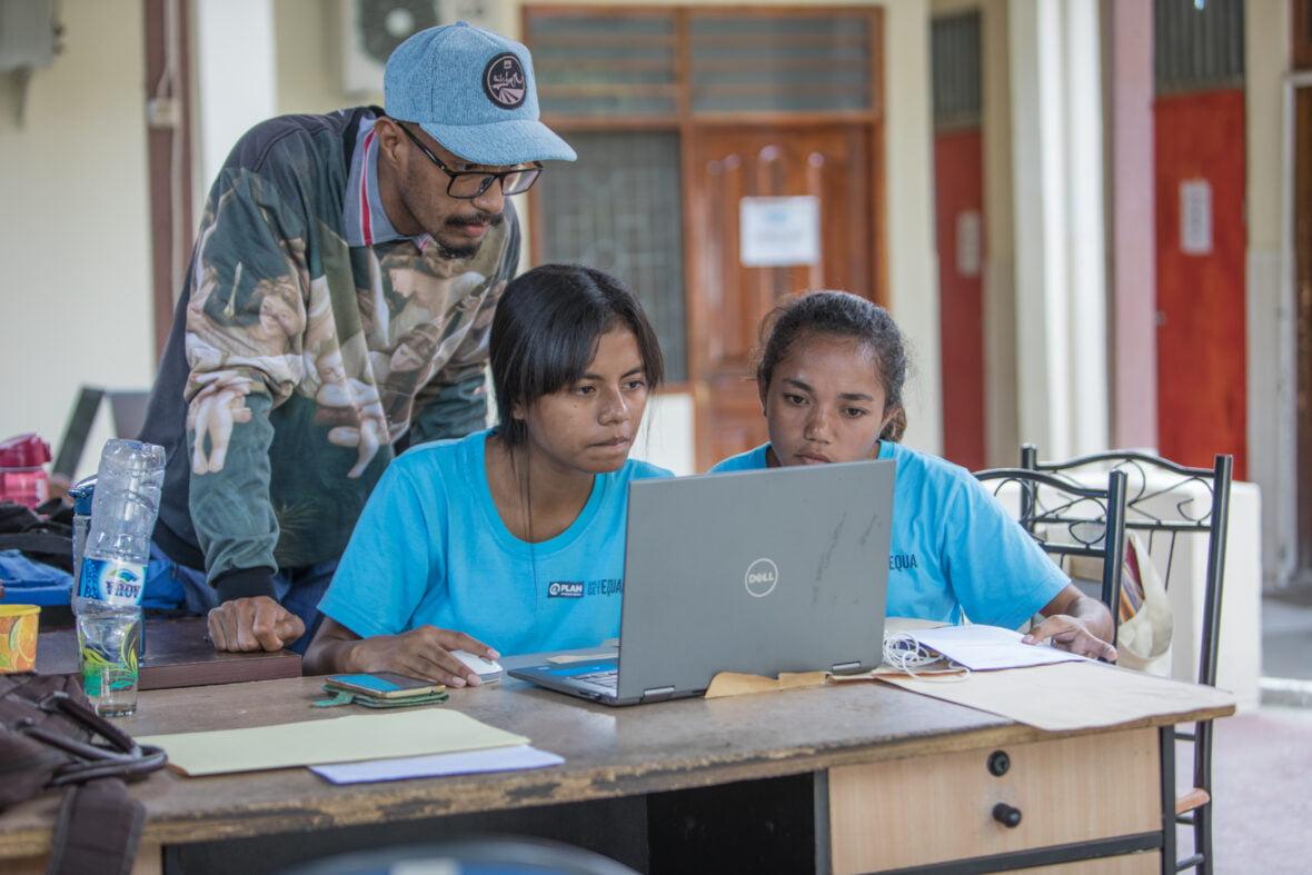 Kolme itätimorilaisnuorta läppärin ääressä Planin toimistolla Itä-Timorissa.