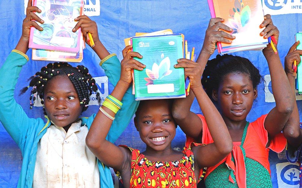 Kolme tyttöä ovat nostaneet koulukirjansa pään yläpuolelle ja katsovat kohti kameraa.