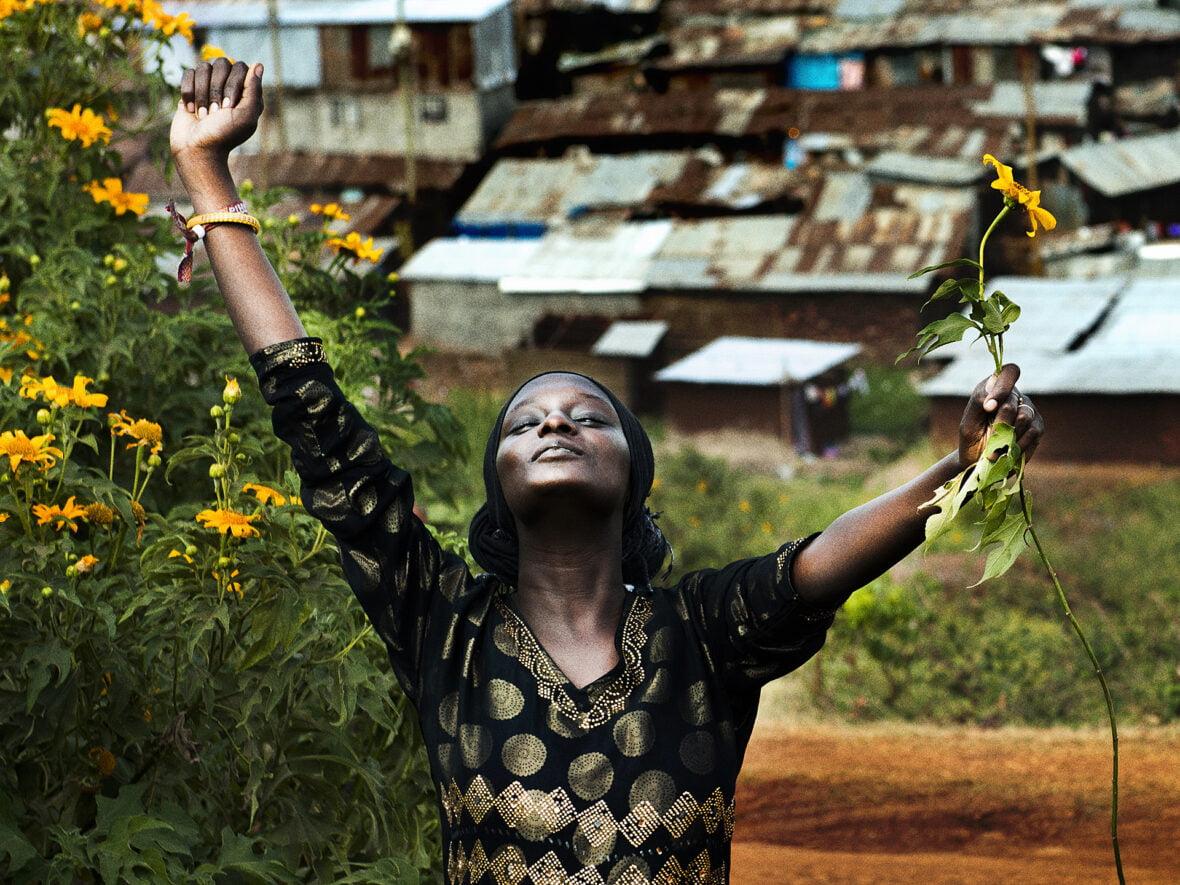 Kenialaistyttö Kiberan slummin edustalla kukka kädessä.