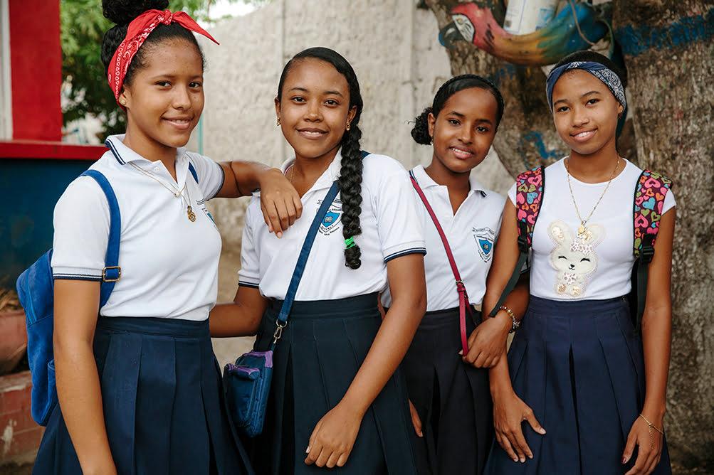 Neljä tyttöä seisoo rinnakkain koulupuvuissa.