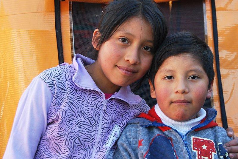Bolivialaiset sisarukset seisovat katsoen kameraan.
