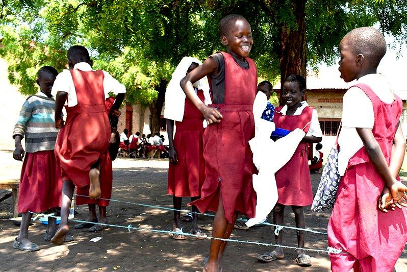 Eteläsudanilaiset tytöt hyppivät hyppynarua yhdessä.