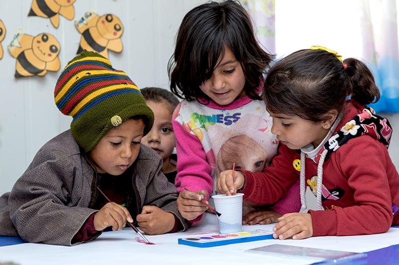 Jordanialaiset lapset ovat kumartuneet pöydän ääreen maalaamaan vesiväreillä.