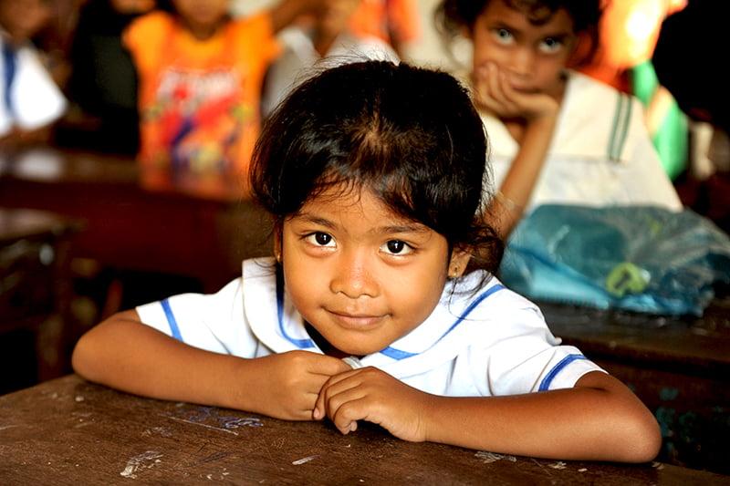 Kambodžalainen tyttö istuu koululuokassa pulpetin ääressä ja katsoo kameraan.