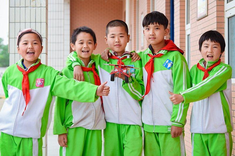 Kiinalaiset lapset esittelevät rakentamaansa robottia koulupn pihalla vihreissä koulupuvuissa.