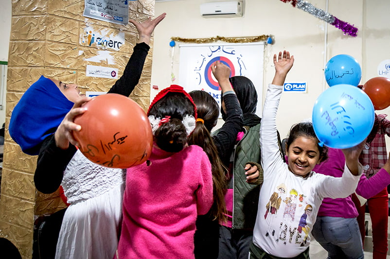 Ryhmä lapsia hyppii ja leikkii ilmapallojen kanssa.