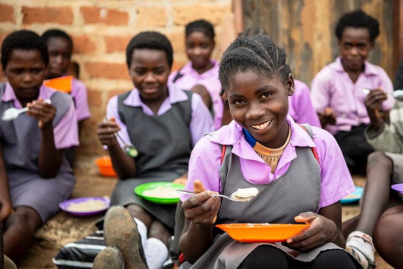 Sambialaiset tytöt ruokailevat pihalla.
