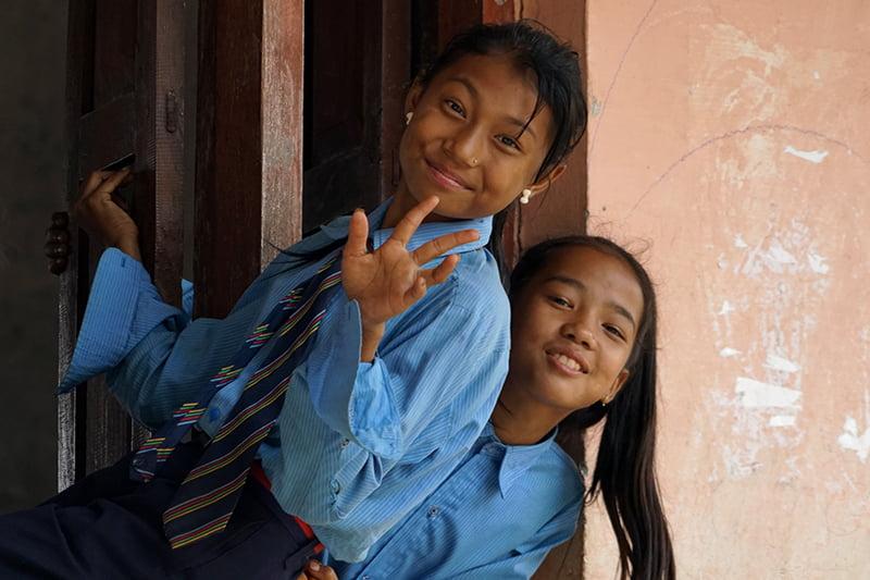 Kaksi koulupukuihin pukeutunutta tyttöä kurkistaa ikkunasta.