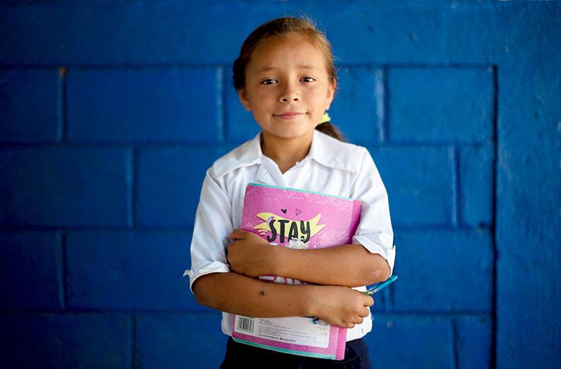 Nicaragualainen tyttö seisoo sinisen seinän edessä kirja sylissään.