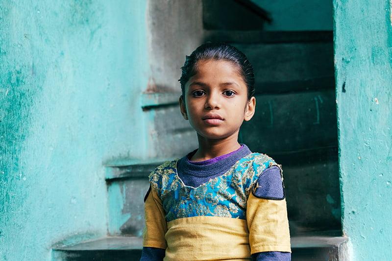 Intialainen tyttö seisoo portaikon edessä ja katsoo kameraan.