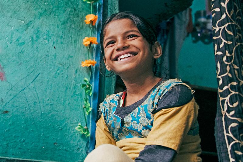 Intialainen tyttö istuu hymyillen turkoosin seinän ja kukkaköynnksen edessä.