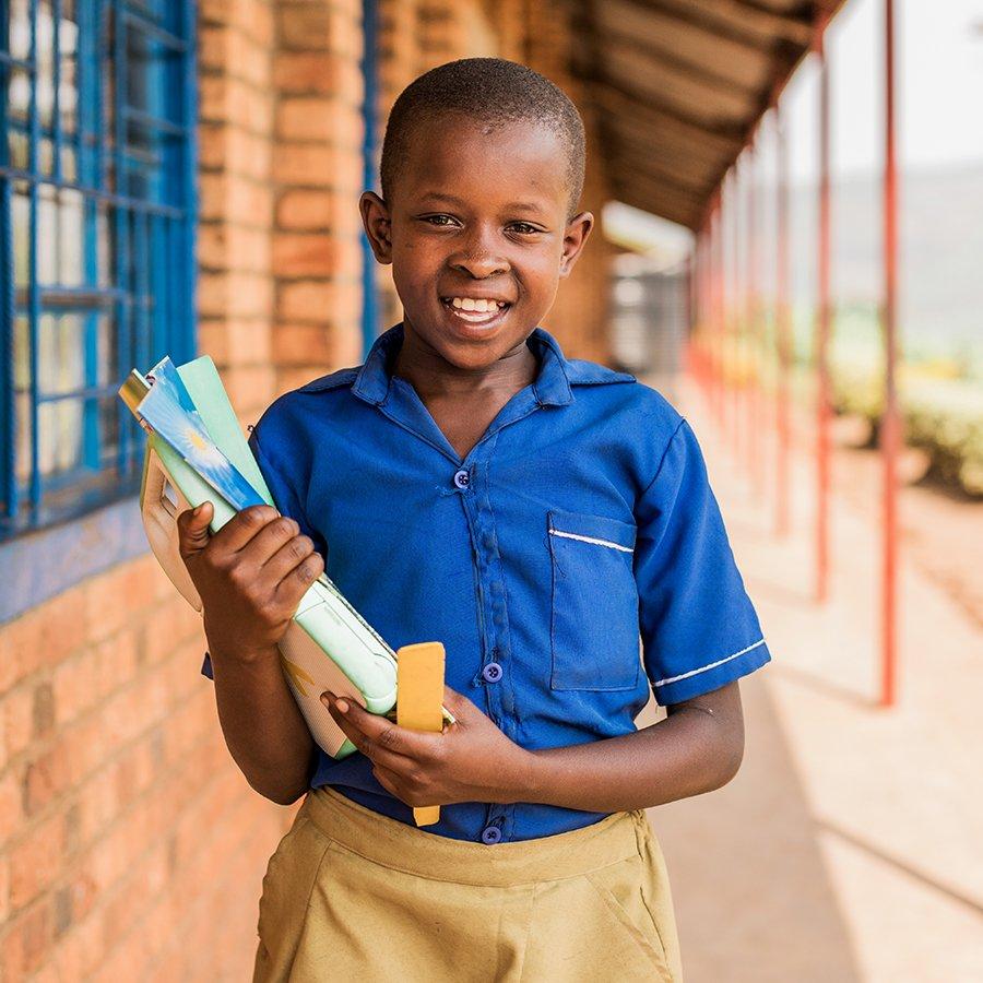 Tyttö on saanut hyväntekeväisyytenä koulutarvikkeita ja seisoo koulun pihalla.