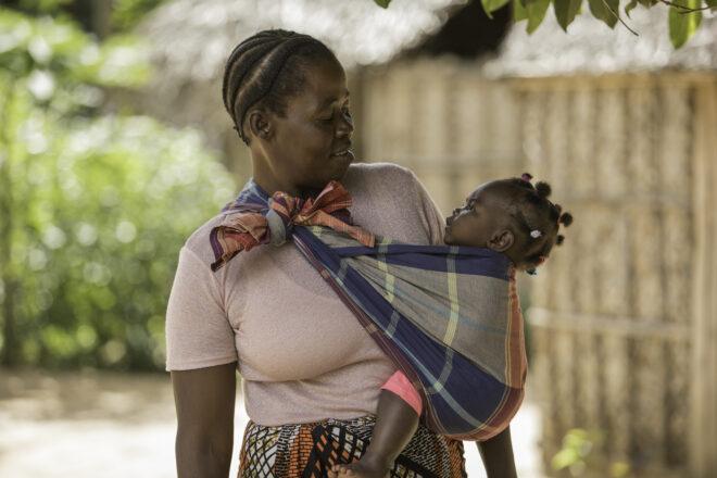 """Isoäiti Aida João, 50, on seitsemän lapsen yksinhuoltaja. Hän on lukutaidoton ja elättää perhettään viljelemällä pientä maatilaa. Aida hoitaa usein pojantytärtään Mairaa, jonka 17-vuotias äiti on muuttanut perheeseen. """"Rakastan miniääni ja vauvaa, mutta minusta on surullista, että teinitytön koulutie katkeaa äitiyteen"""", Aida kertoo."""