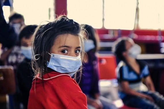 Honduraslilainen tyttö katsoo olkansa yli kasvpmaski kasvoillaan.