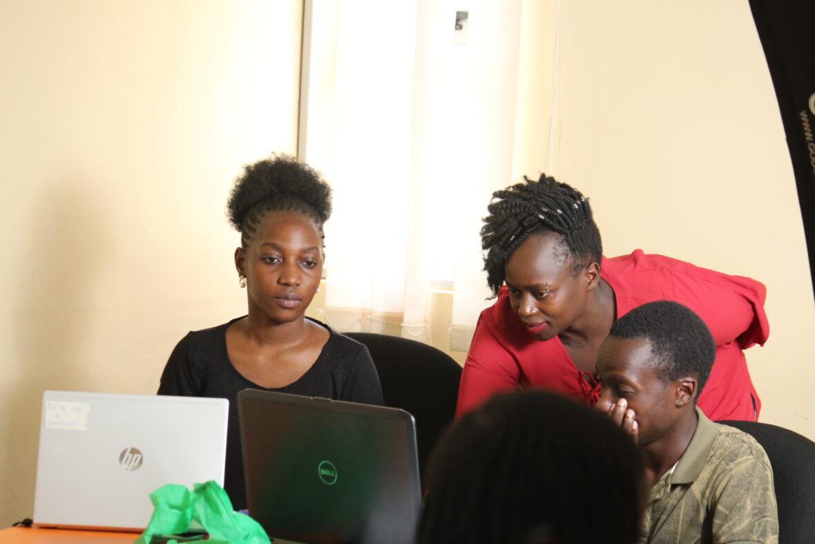 Kaksi nuorta istuu tietokoneen äärellä ja kolmas esittelee heille jotain koneelta.