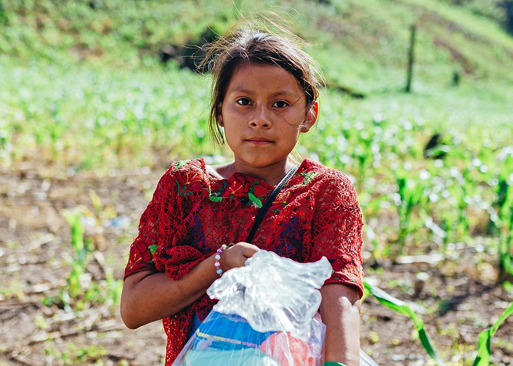 Tyttö seisoo pellolla ja pitelee sylissään ruoka-apupakkausta.