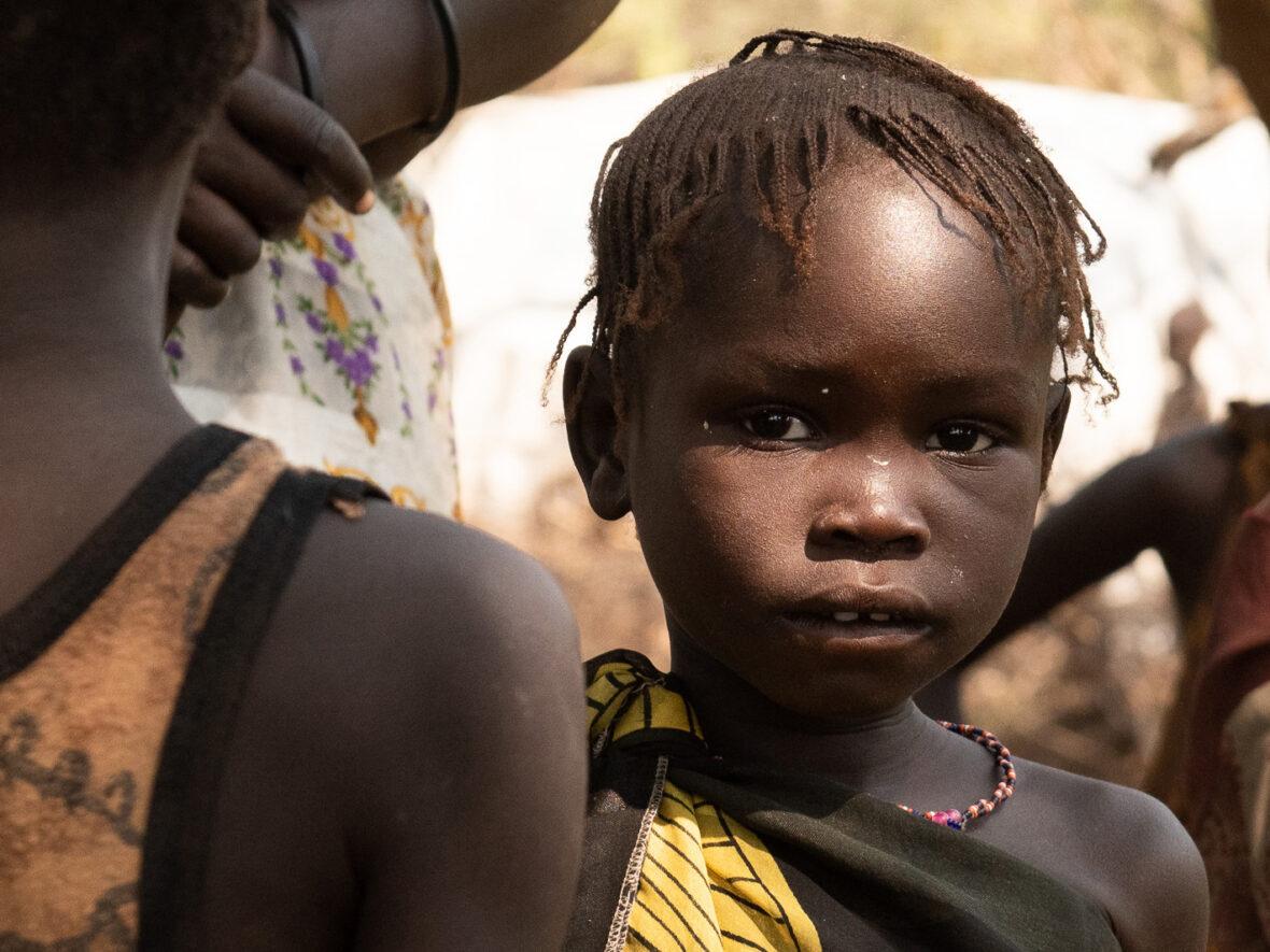 Eteläsudanilainen tyttö katsoo vakavana kameraan.