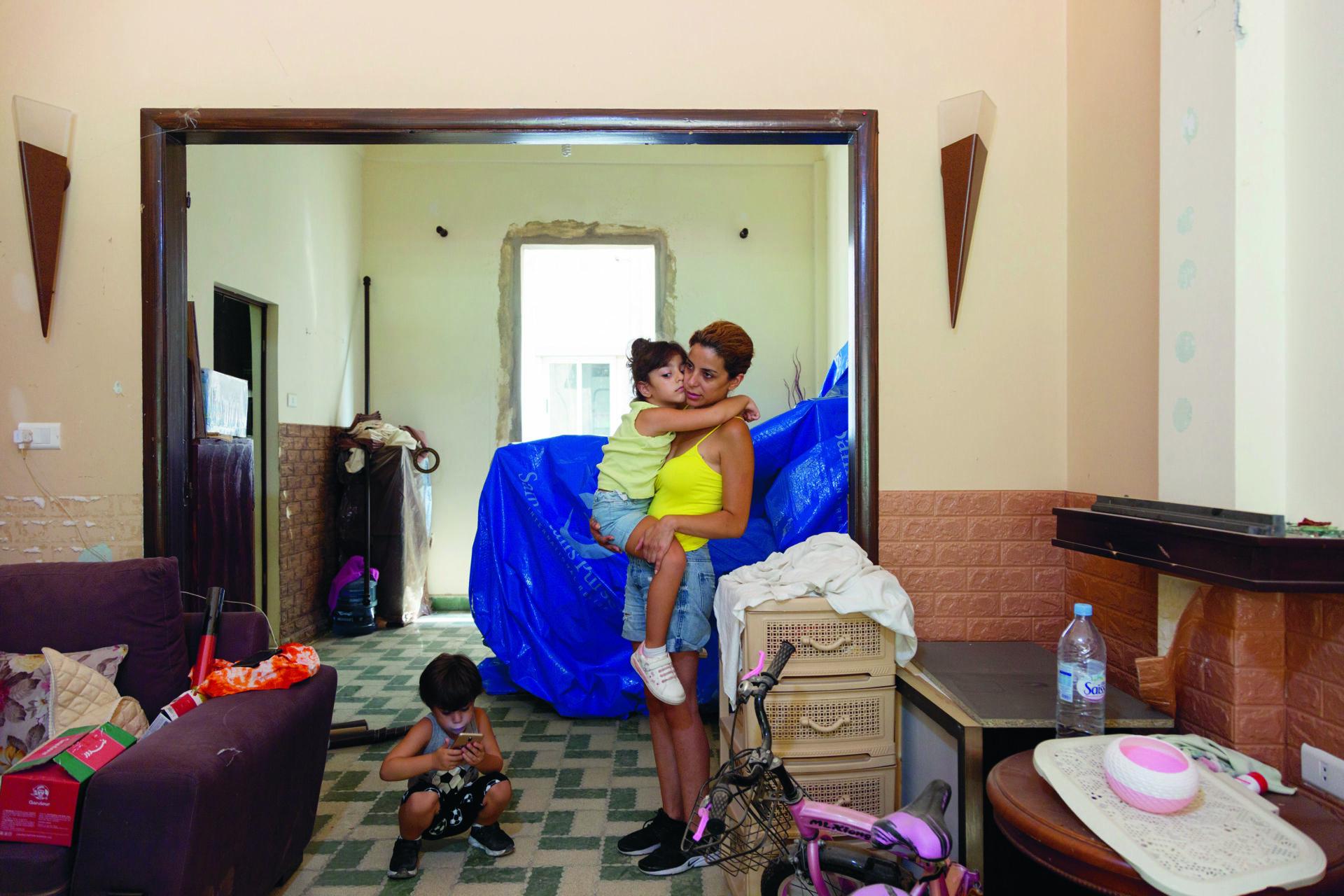 Beirutilainen nainen lapsi sylissään räjähdyksen jälkeen