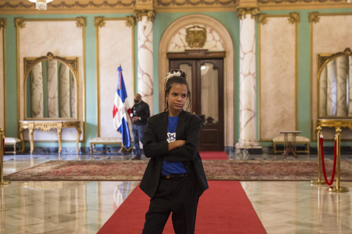 Melany, 10, pikkutakissa seisoo punaisella matolla Dominikaanisen tasavallan presidentin työtiloissa.