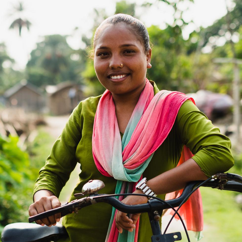 20-vuotias nepalilainen Laxmi nojaa polkupyöräänsä ja katsoo hymyillen kameraan