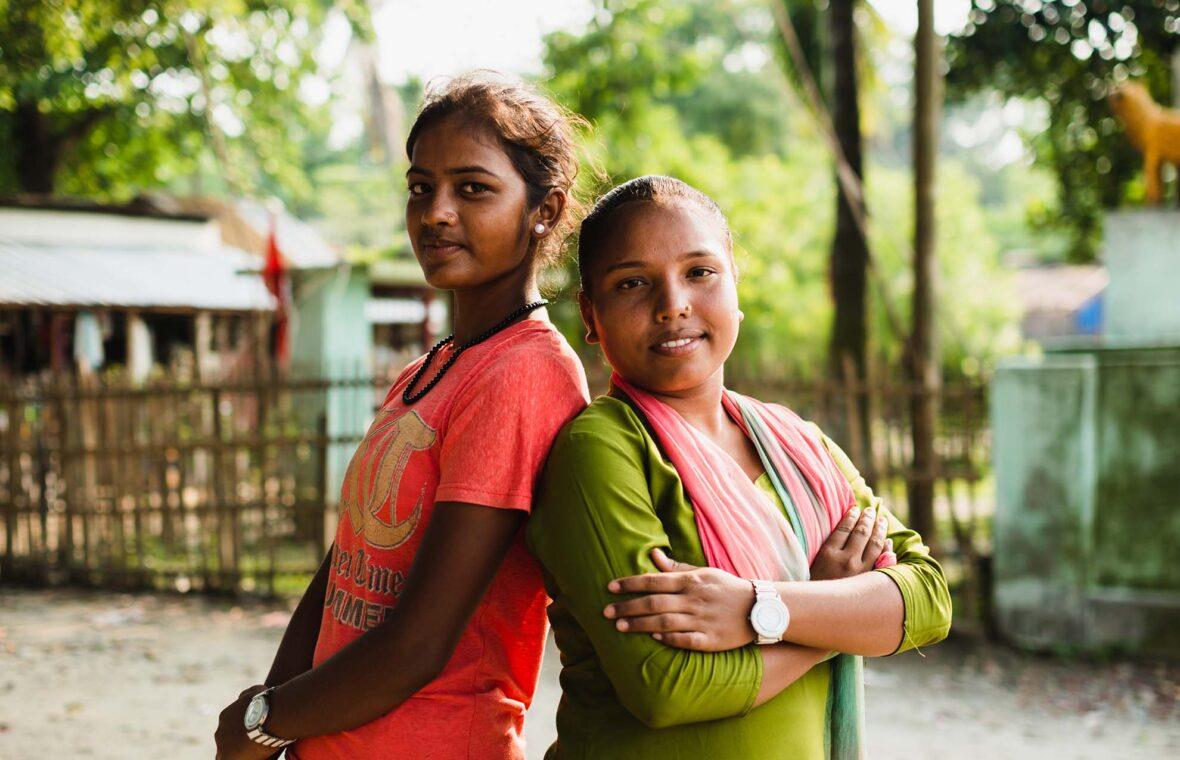 Nepalilaiset tytöt seisovat selät vastakkain.