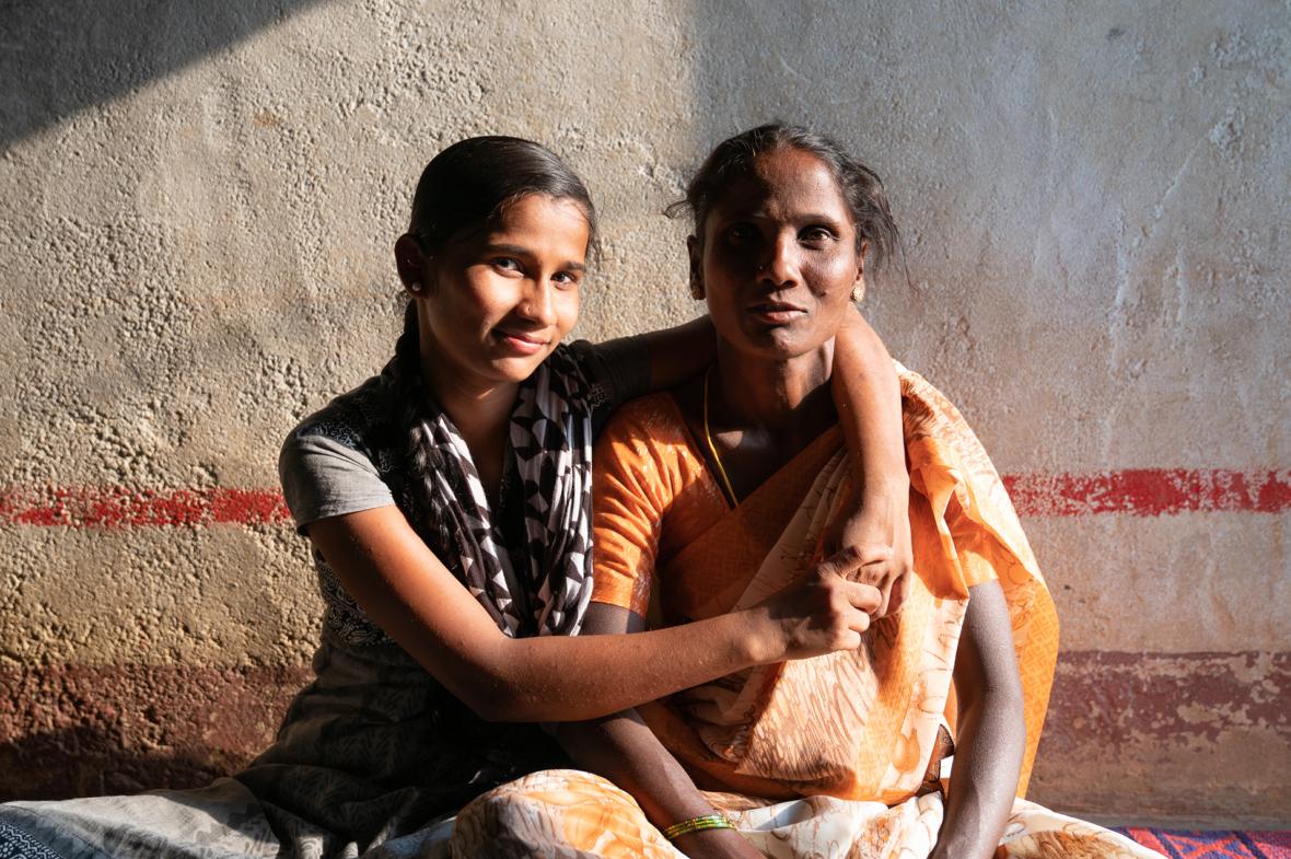 Intialainen tyttö ja hänen äitinsä istuvat vierekkäin lattialla.