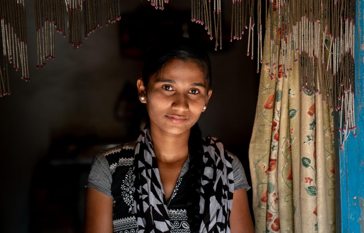 Intialainen tyttö seisoo hämärssä huoneessa ja katsoo kameraan.