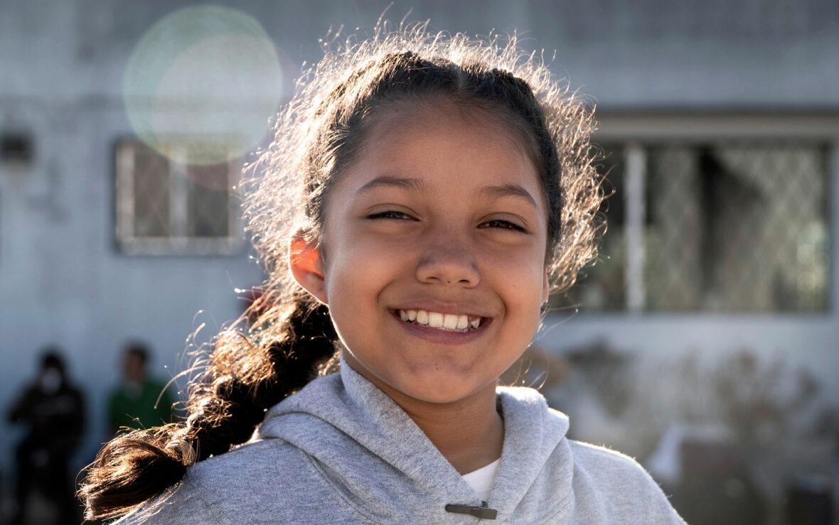 Ecuadorilainen tyttö hymyilee auringonpaisteessa.