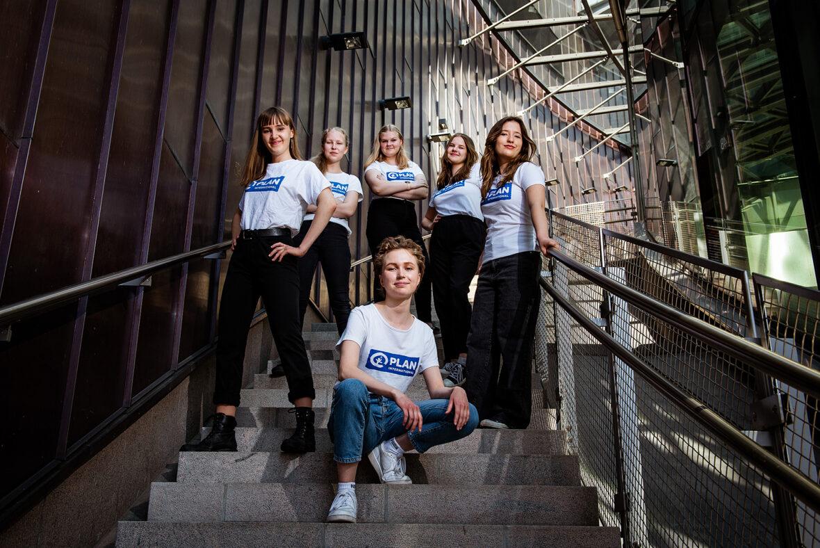 Kuusi nuorta tyttöä Planin t-paidoissa seisoo rappusissa ja poseeraa kameralle.