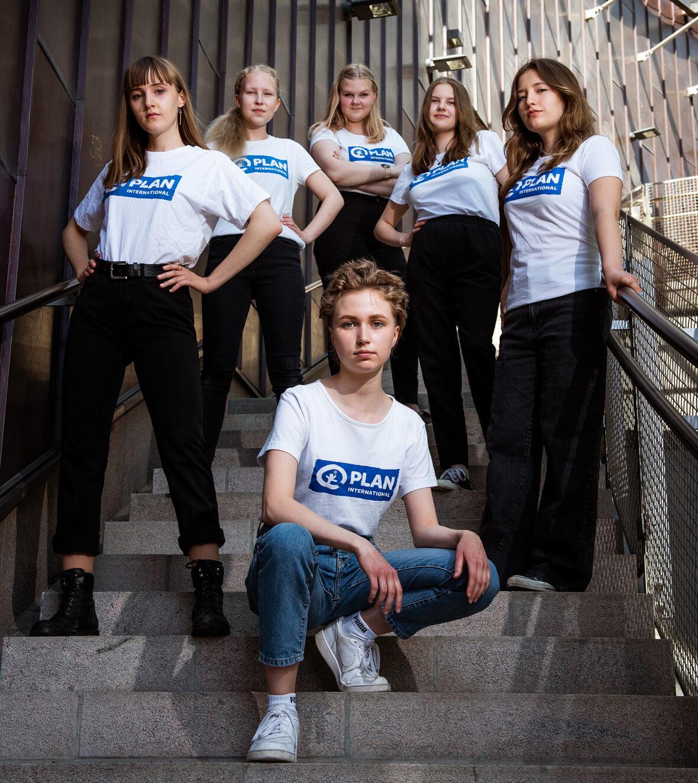 Kuusi nuorta tyttöä Planin t-paidoissa seisoo rappusissa ja poseeraa kameralle. Kuvan päällä #GirlsTakeover-logo
