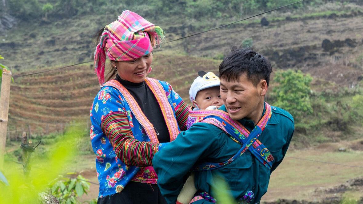 Nainen asettelee pientä lasta miehen selkään kantoreppuun pellon laidalla.