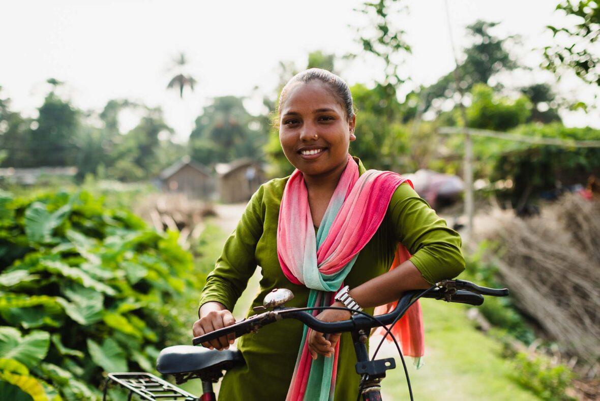 Nepalilainen tyttö seisoo vehreässä maisemassa ja nojaa pyöräänsä.