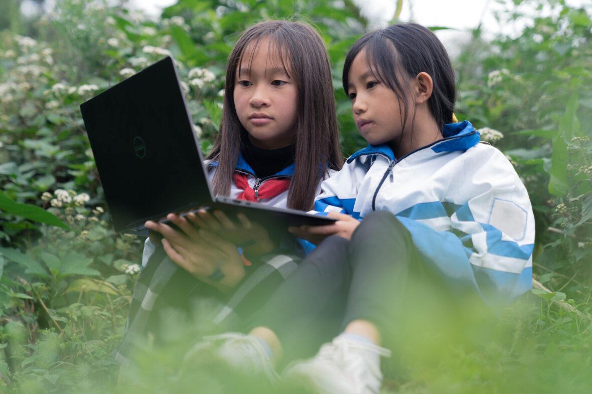 Kaksi vietnamilaista lasta istuvat tietokoneen ääressä.