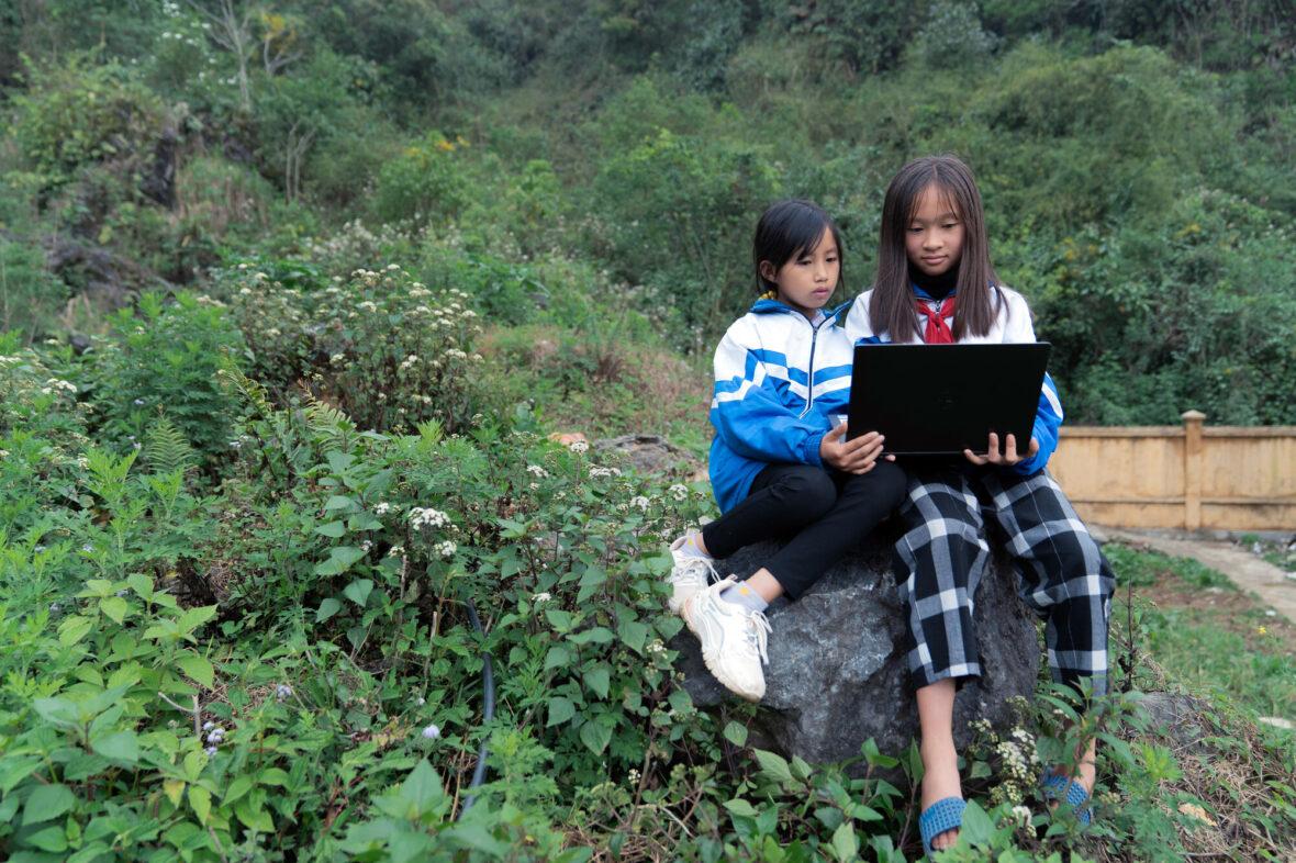 Kaksi vietnamilaista lasta istuu kivellä ja käyttää tietokonetta.